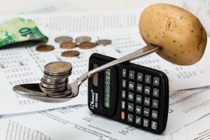 на ложке картошка и монеты