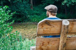 унылый человек сидит на лавке