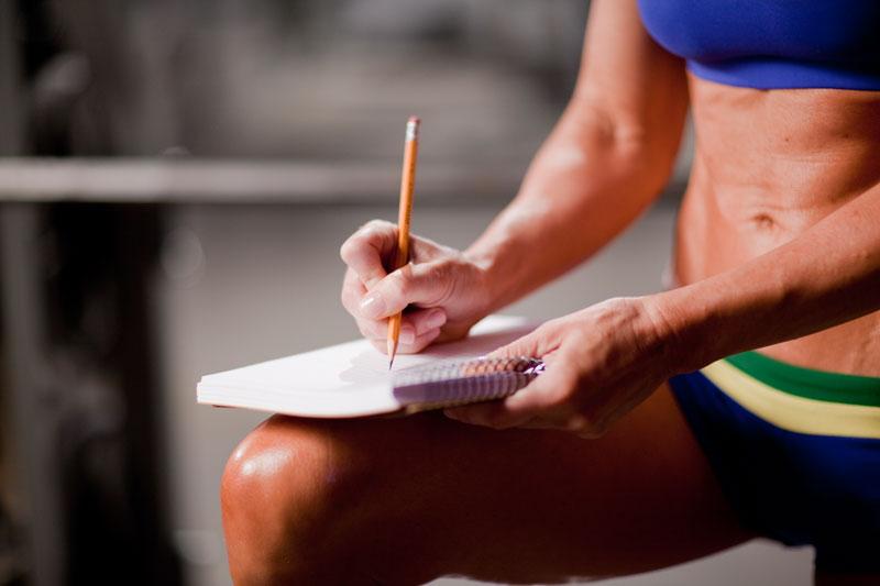 спортсмен делает запись в журнале