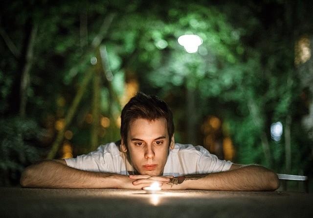 парень смотрит на свечу