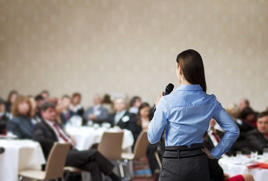 Девушка говорит в микрофон перед публикой
