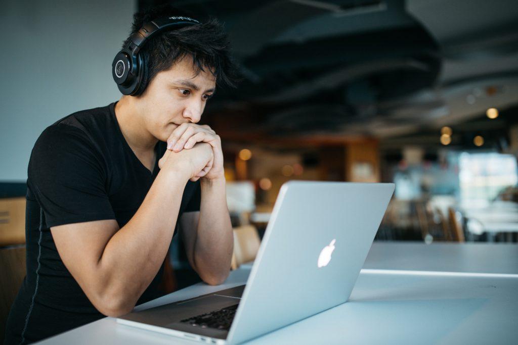 Студент слушает обучающий курс в наушниках